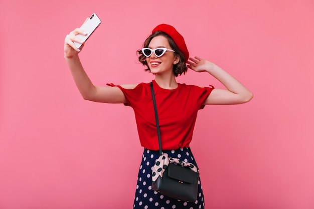 Selfie를 만드는 귀여운 문신과 쾌활 한 유럽 소녀. 베레모와 선글라스에 멋진 프랑스 여성이 자신의 사진을 찍습니다.
