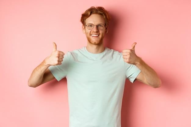 Веселый европейский мужчина с рыжими волосами и бородой, в очках, показывая большие пальцы руки и улыбаясь в знак одобрения, хвалит что-то хорошее, стоя на розовом фоне.