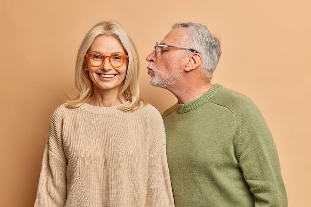 Cheerful european middle aged woman smiles gently as receives kiss from husband have good relationships love each other for long time isolated over brown wall