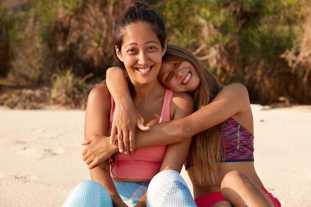 陽気なヨーロッパの女性は彼女の仲間を抱きしめ、一緒にスポーツトレーニングをし、ビーチに座っています