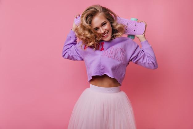 Веселая европейская женщина держит скейтборд и смешно смеется. удивительная блондинка развлекается пастелью.