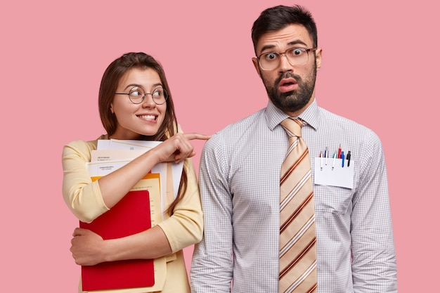Cheerful european woman holds folder with papers, touches shoulder of embarrassed director, do paper work together, face financial problem of company, both wear spectacles. office workers indoor