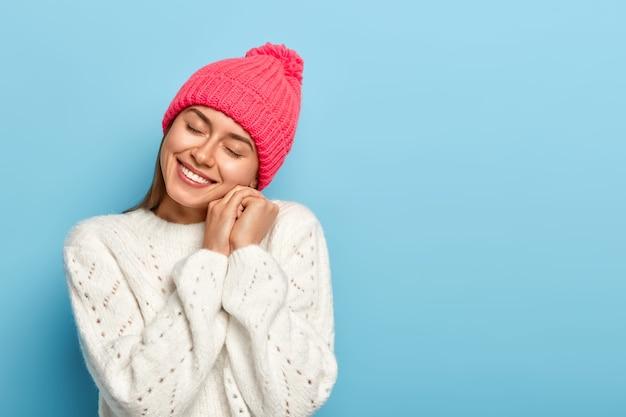 Allegra donna europea ricorda bei ricordi piacevoli, inclina la testa, tiene le mani vicino al viso, sorride felice, indossa un cappello lavorato a maglia roseo e un maglione bianco, posa su sfondo blu.