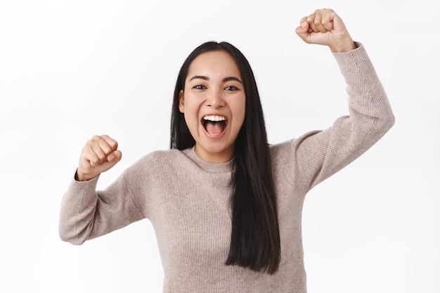 Allegra ragazza asiatica eccitata che fa il tifo per la squadra di calcio, alza le mani in alto, pompa a pugno e sorride, grida dall'adorazione e dal brivido, il fan devoto vuole vincere. donna che trionfa come competizione per diventare campione