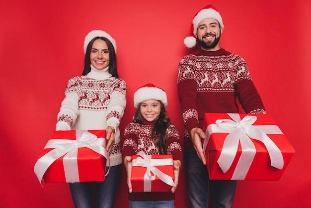 Веселые возбужденные красивые родственники держат подарки в вязаных традиционных костюмах