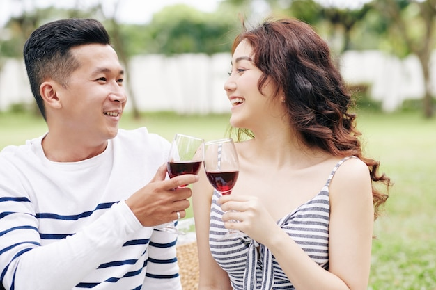 Cheerful excited boyfrend and girlfriend toasting with wine glasses and looking at each other