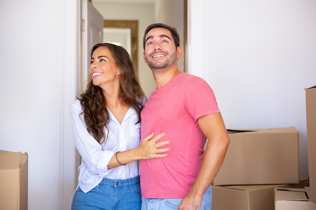 Cheerful excited couple moving into new house, standing among carton box, hugging and looking around