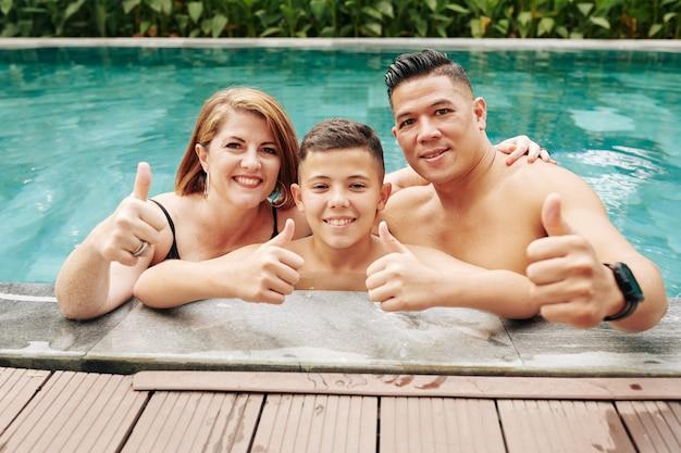Веселый взволнованный отец, мать и сын, стоя в бассейне и показывая большие пальцы руки