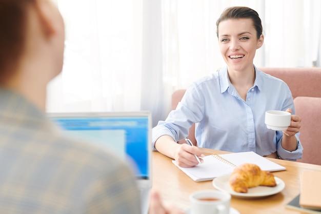 ランチで同僚とやり取りしながら、コーヒーを飲みながらノートに書く陽気な興奮したフレンドリーなビジネス女性