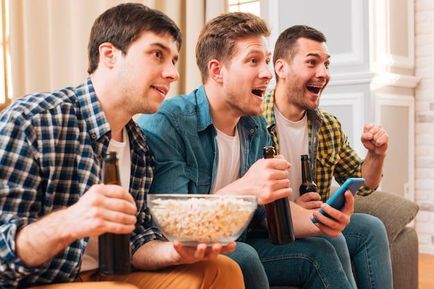 Веселые возбужденные друзья держат в руках пивные бутылки и смотрят матч по телевизору