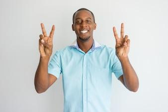 Cheerful excited handsome African man showing peace signs and looking at camera.