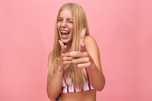 ゆるいストレートヘアウインク、前指を前に向け、機嫌が良い陽気な興奮したヒップスターの女の子。楽しんでいるスタイリッシュな若い白人女性