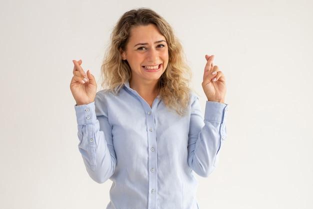 Веселая возбужденная дама в синей блузке, пересекающей пальцы для надежды
