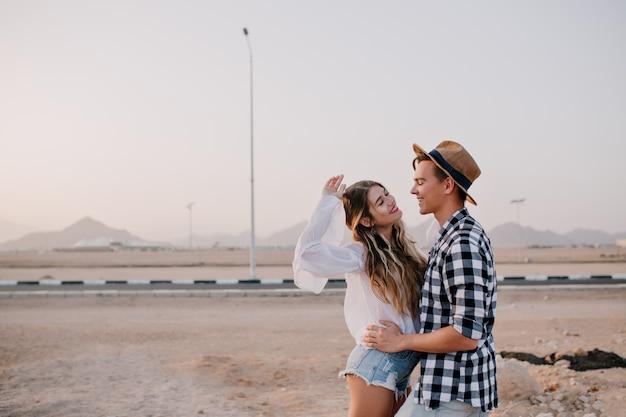 陽気な興奮した髪の長い女性が彼女のスタイリッシュなボーイフレンドと夜明けの空の下でポーズします。早朝に道の近くに立って笑っているガールフレンドを抱きしめるトレンディな帽子の若い男