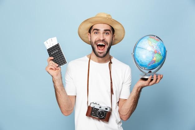 青い壁の上に孤立して立って、チケットと地球儀とパスポートを示す空白のtシャツを着て陽気な興奮した男
