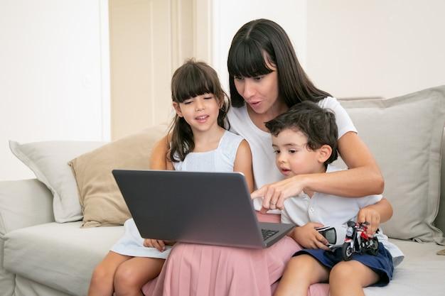 幸せな子供を抱き締めるとノートパソコンの画面を指して陽気な興奮しているママ。家族が自宅のソファに座って映画を見ています。