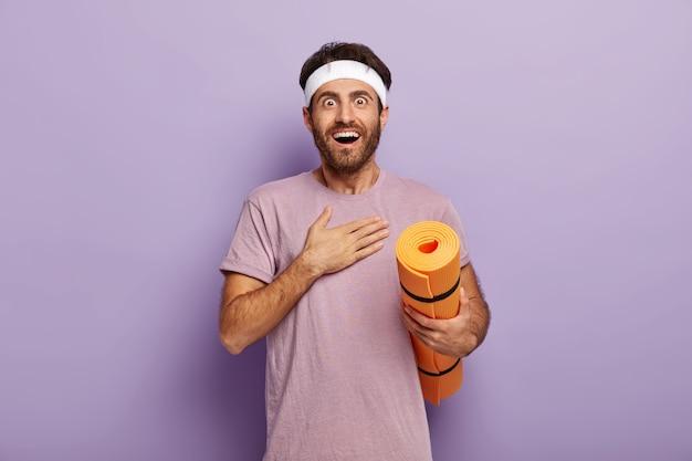 쾌활한 흥분된 스포츠맨은 놀라움으로 보이고, 가슴을 만지고, 매일 요가를 연습합니다.