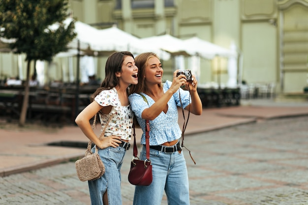 Cheerful excited tanned girls in stylish floral blouses and denim pants smile sincerely outside