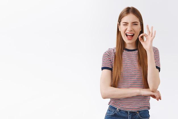 Жизнерадостная, возбужденная женщина в полосатой футболке не беспокоится, чувствует себя уверенно и расслабленно, показывает нормально, соглашается, знак кокетливо подмигивает, дает положительный ответ, довольная стоя на белом фоне