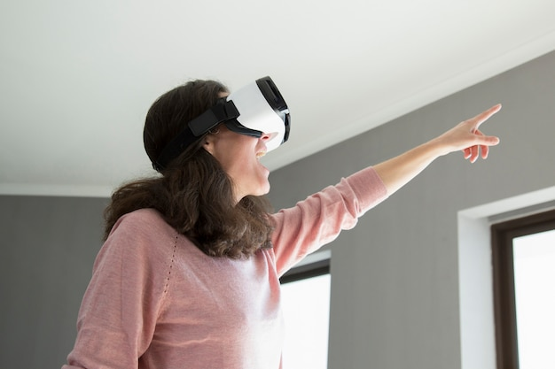 Cheerful excited woman in vr goggles pointing aside