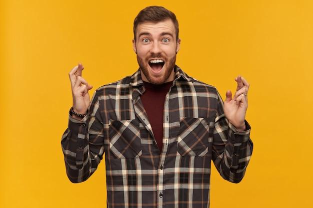 指を交差させて立って、黄色の壁に願い事をしている開いた口を持つ市松模様のシャツを着た陽気な興奮した若いひげを生やした男