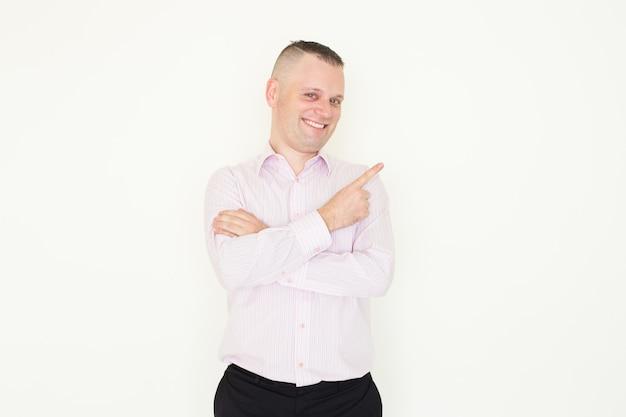Веселый возбужденный молодой бизнесмен, указывая в сторону и глядя на камеру.