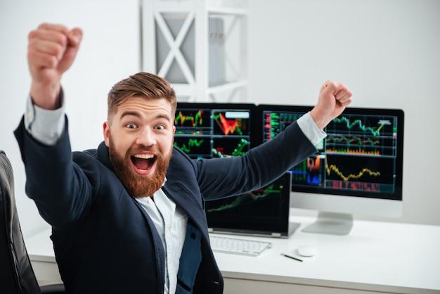 Веселый возбужденный молодой бизнесмен с поднятыми руками кричит и празднует успех на рабочем месте в офисе