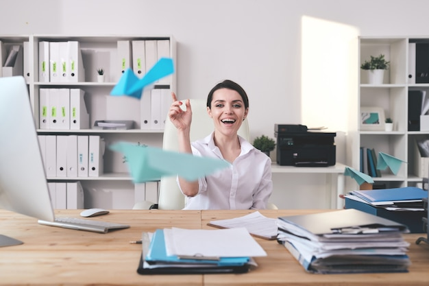 Cheerful excited young businesswoman sitting at desk full of documents and throwing paper plane in office