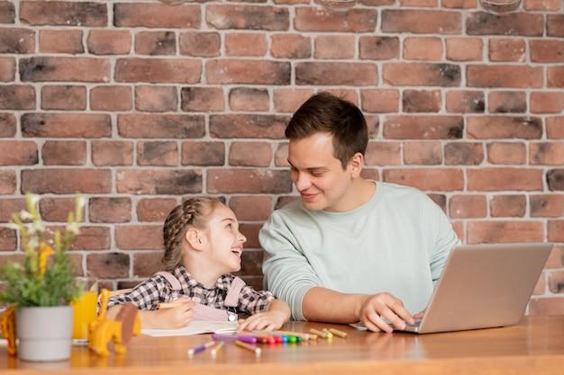 Веселый возбужденный молодой отец и красивая дочь с косой сидят за столом в квартире-лофте и вместе работают над школьным проектом, используя разноцветные карандаши и ноутбук