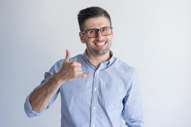 Веселый возбужденный молодой мужчина-менеджер показывает мне жест и смотрит на камеру.