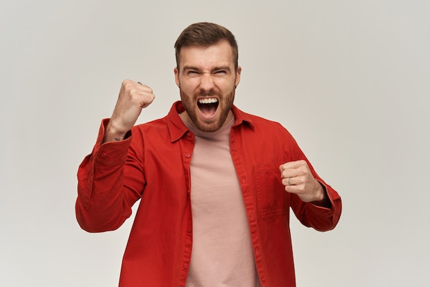 Cheerful excited young man in red shirt with beard keeps fists clenched and raised hands and screaming over white wall celebrating victory concept