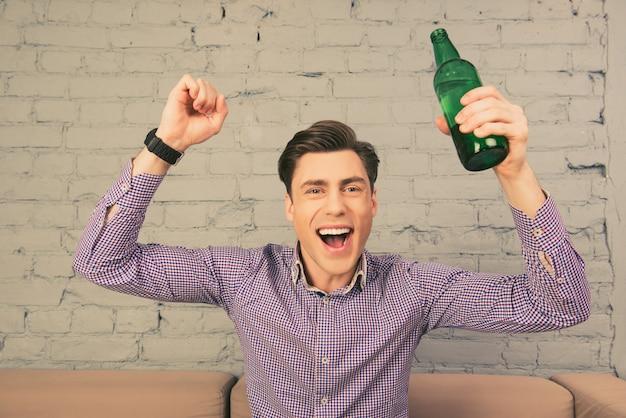 ビールでサッカーを見ている陽気な興奮した若い男