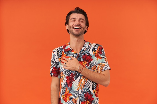 Cheerful excited young man with bristle and closed eyes in colourful shirt keeps hand on chest and feels relief