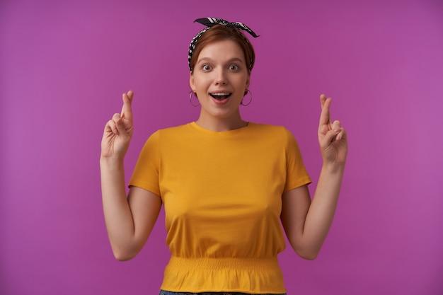 머리에 머리띠가 달린 노란색 티셔츠에 쾌활한 흥분된 젊은 여성이 손가락을 엇갈리게 유지하고 보라색 벽에 영감을 얻은 것 같습니다.
