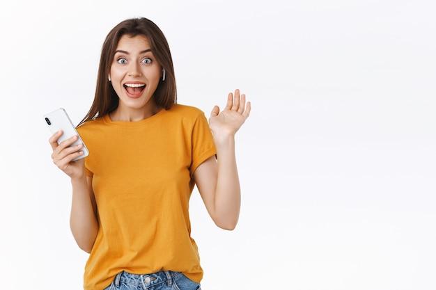 쾌활하고 흥분한 젊은 여성은 생일 선물로 무선 이어폰을 받고, 행복을 숨길 수 없고, 흥분되고 행복한 악수를 하고, 스마트폰을 들고, 헤드폰으로 음악을 듣습니다.
