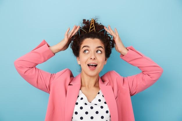 유니콘 왕관을 쓰고 파란 벽 위에 고립된 채 서 있는 쾌활한 흥분한 젊은 여성