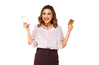 Cheerful excited young woman with mobile phone and credit card posing