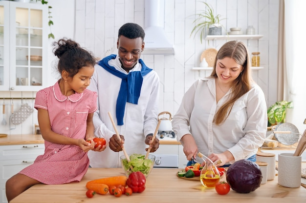 朝食に野菜サラダを調理する陽気な家族。朝の台所で母、父と娘、良い関係