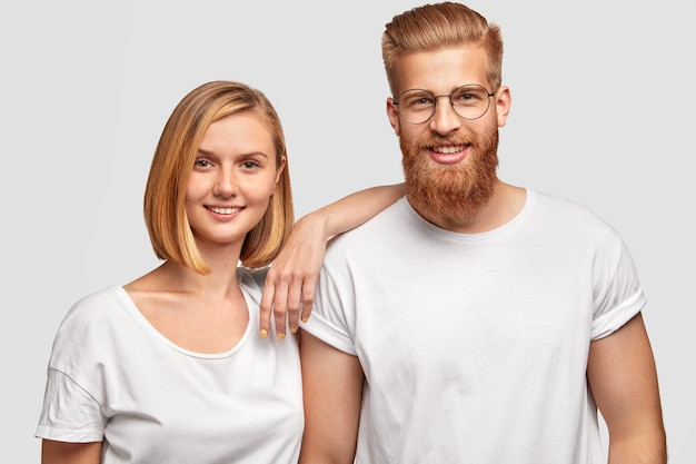 Cheerful family couple rejoice they become parents soon, stad close to each other, dressed in casual clothes, isolated over white wall. happy bearded male has date with pretty young female