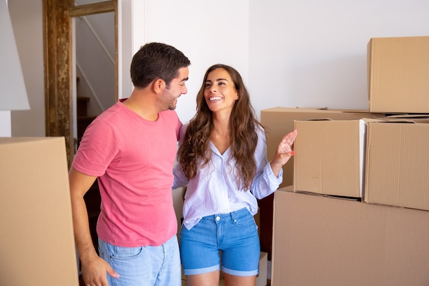 Cheerful family couple standing among carton boxes, hugging and discussing their new apartment
