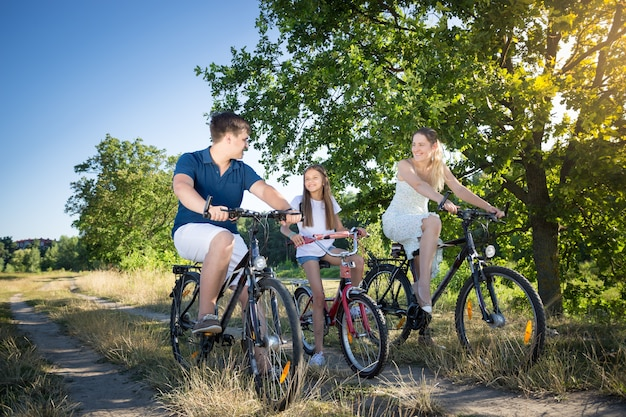 Cheerful family cycling in meadow at hot sunny day