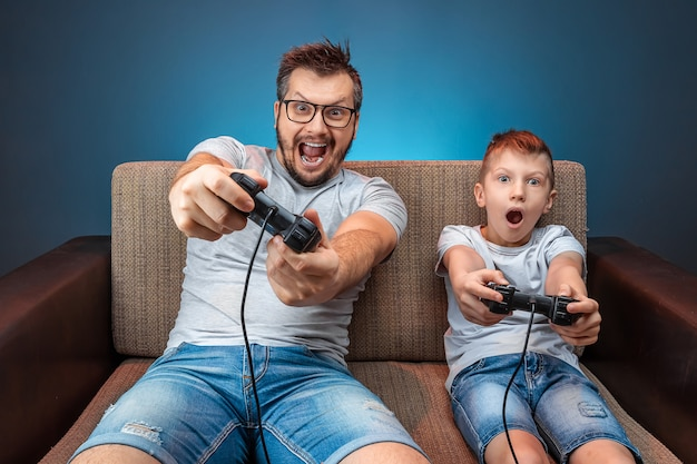 A cheerful family, dad and son play on the console, in video games, emotionally react while sitting on the couch. day off, entertainment, leisure, spend time together.