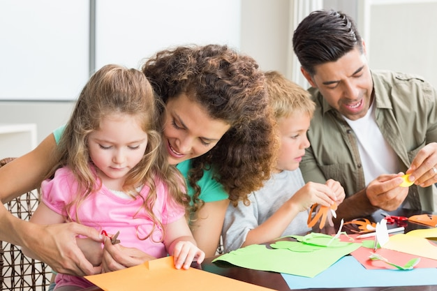 Веселая семья, занимающаяся искусством и ремеслом вместе за столом
