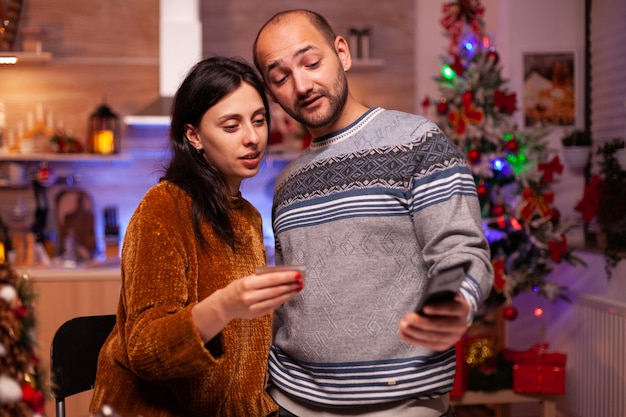 Cheerful family doing online shopping xmas gift using credit card for payment