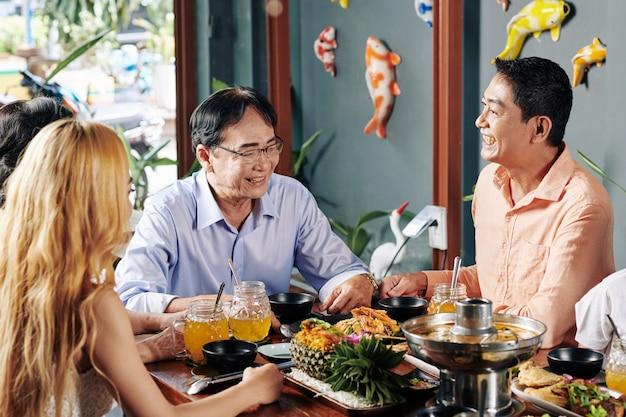 Веселая семья обедает в ресторане