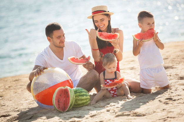 Cheerful family eating watermelon on the beach. little kids and their parents on the sea shore having fun. joyful family on the seaside