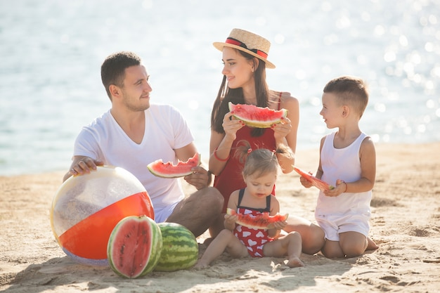 ビーチでスイカを食べて元気な家族。楽しい海岸で小さな子供たちとその両親。海辺のうれしそうな家族