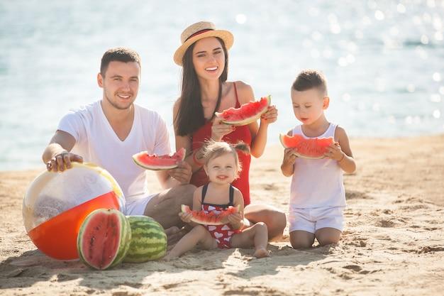 Веселая семья ест арбуз на пляже. маленькие дети и их родители на берегу моря веселятся. радостная семья на берегу моря
