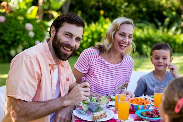 Веселая семья наслаждается завтраком во дворе