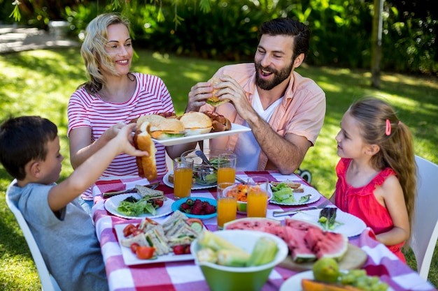 Веселая семья наслаждается едой во дворе